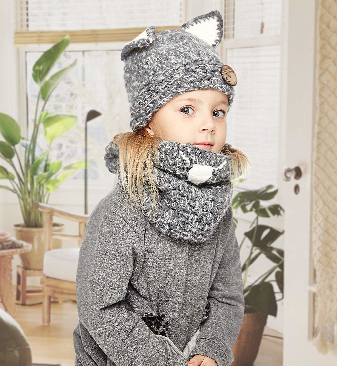 child model in grey scarf and hat with pointed animal ears