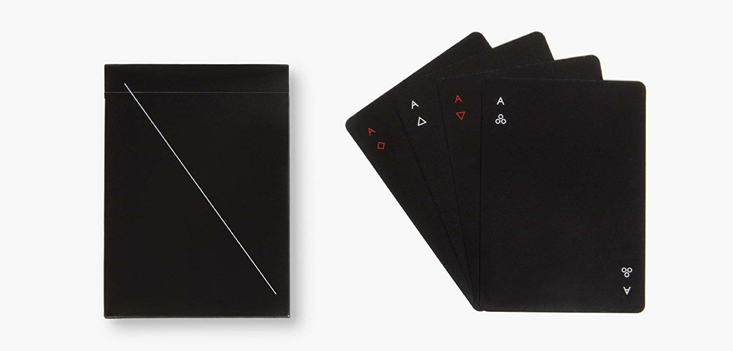 A set of black playing cards with simple red and white suit markers in the corners