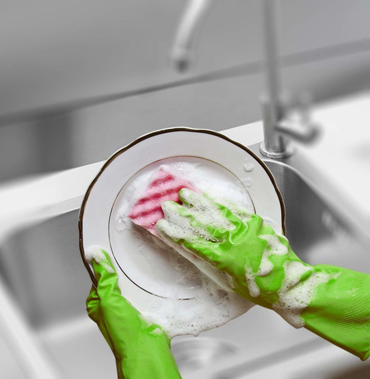 Hands in green rubber gloves cleaning dishes