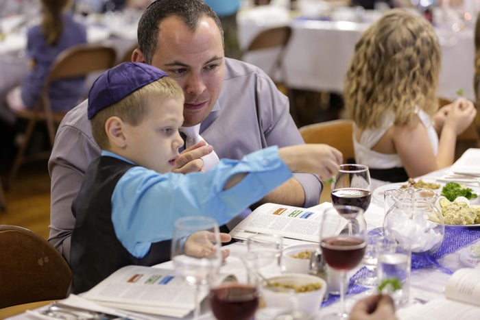 Shawn Soifer instructs his son to dip parsley from the Seder Plate in a cup of salt water during the Seder meal Friday night at Adas Israel in Mason City, Iowa on April 22, 2016