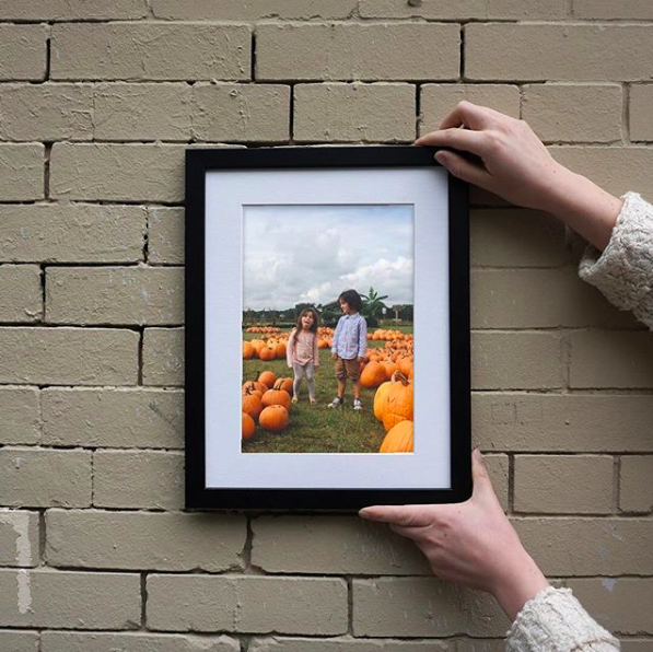 person holding up a framed pic of two kids standing in a pumpkin patch