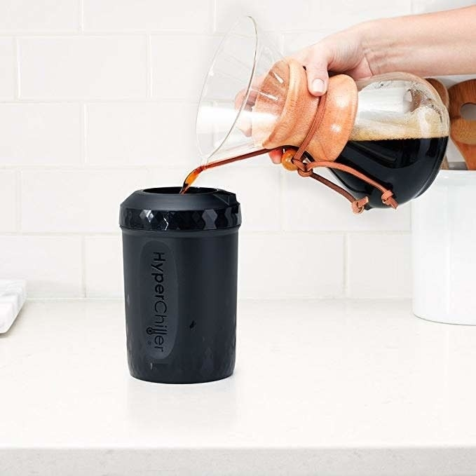 The black cylinder HyperChiller with a circular hole in the top with a carafe of coffee being poured into it
