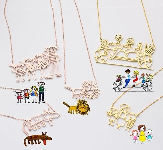 Several children's drawings next to rose gold and gold pendant necklaces of them