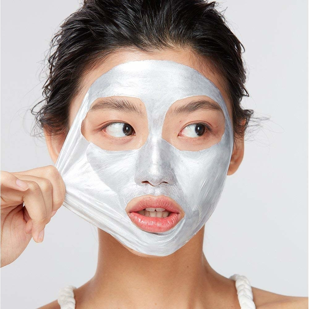 silvery face being peeled off model's face