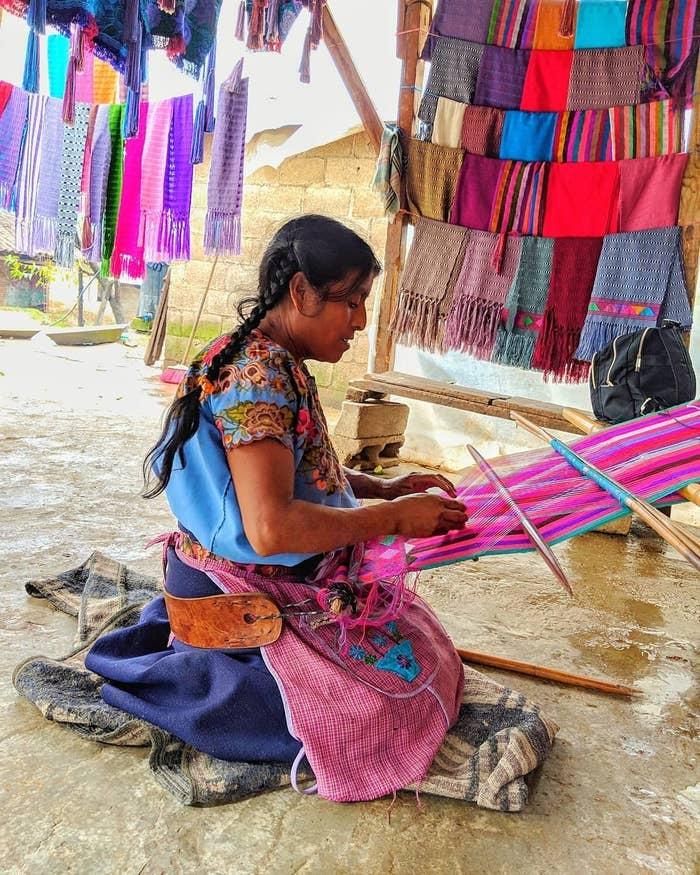 Utilizando su propio cuerpo para mover los hilos en un aparato formado por dos barras de madera, las artesanas crean coloridas formas sobre la tela.