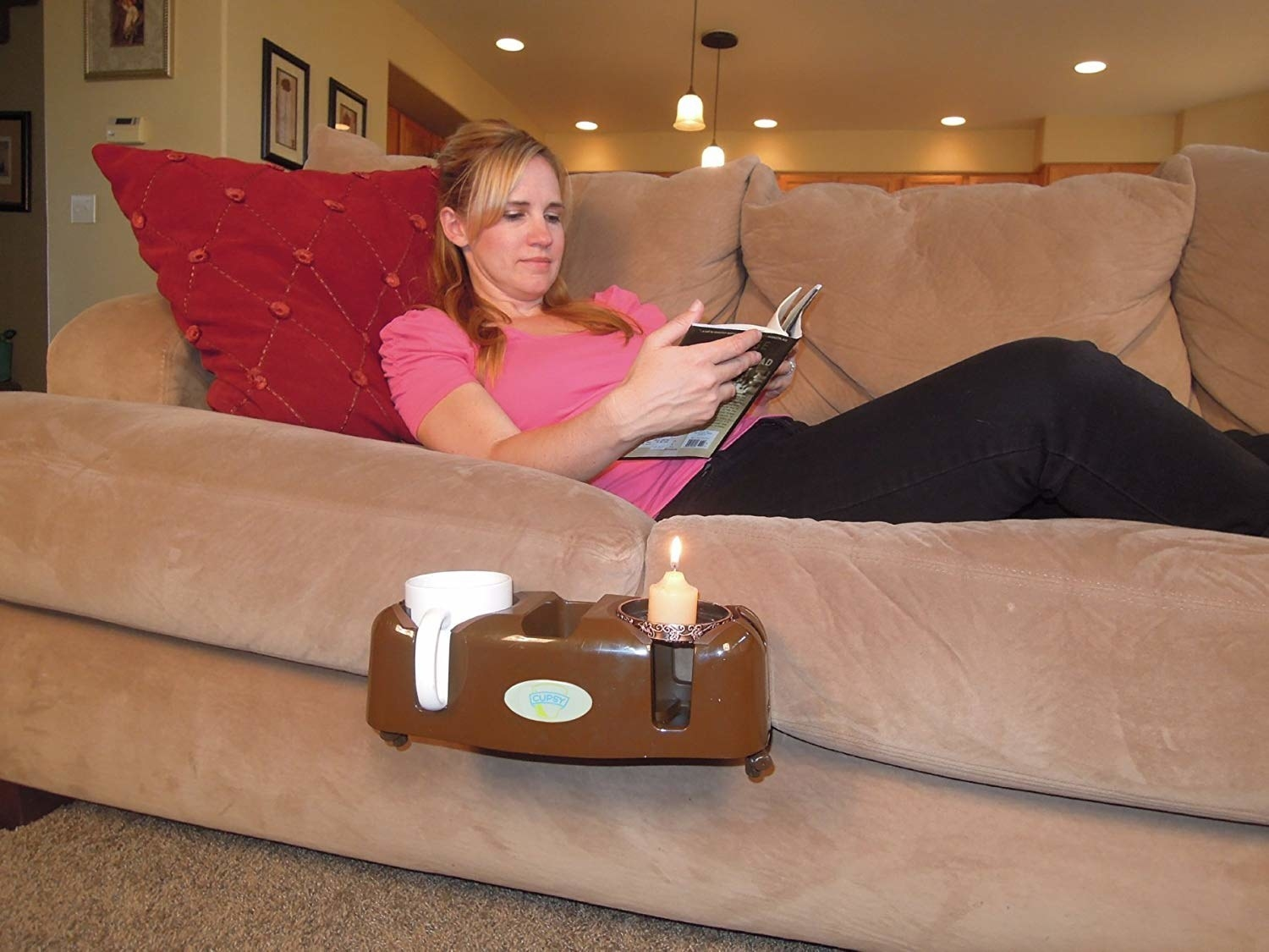 The oval-shaped couch caddy in brown with two cup holders and a smaller holder in the center attached to the side of a couch with a model lying and reading above it