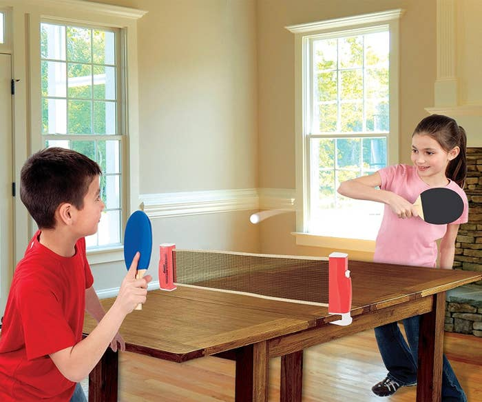 Two kids playing ping pong with a net over a wooden table