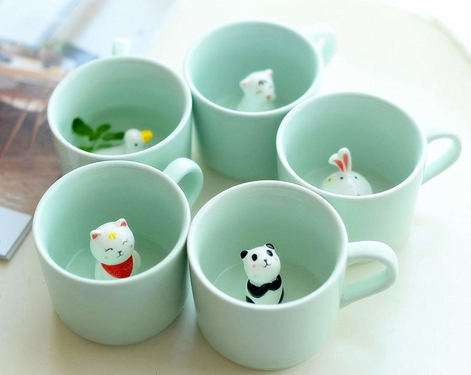 five of the small mint mugs, with a duck, cat, panda, bunny, and tiger figure at the bottom of them