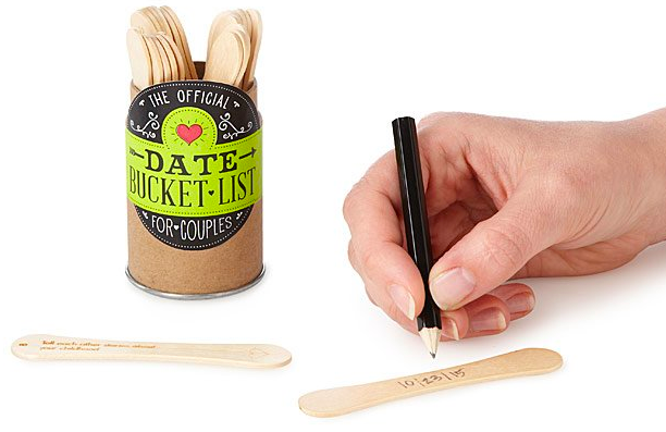 Person writing on stick with provided pencil with several others inside decorative tube