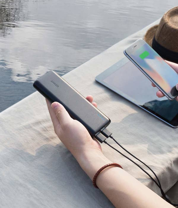 Hand holding the thin rectangle-shaped charger with a cord connecting to a phone, showing that it's charging