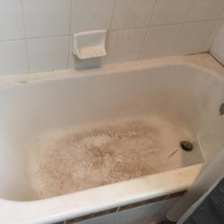 A review photo of a dirty, stained tub