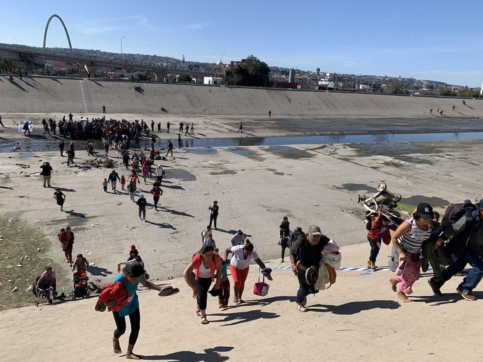 Migrants crossing the Tijuana River as they approach the US border.