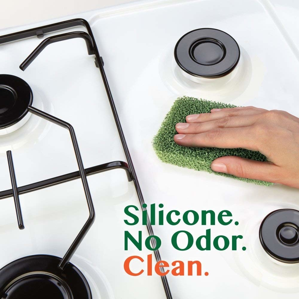 """Hand using the sponge on a gas cooktop with text """"silicone. no odor. clean"""""""