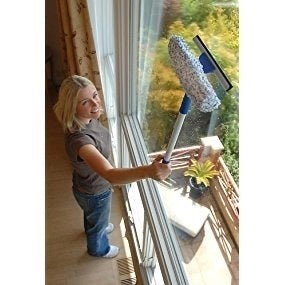 a person using the sponge on an indoor window