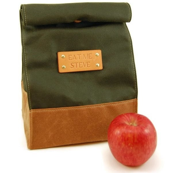 "The leather and fabric roll-top lunch bag that says ""eat me steve"" on the nameplate"