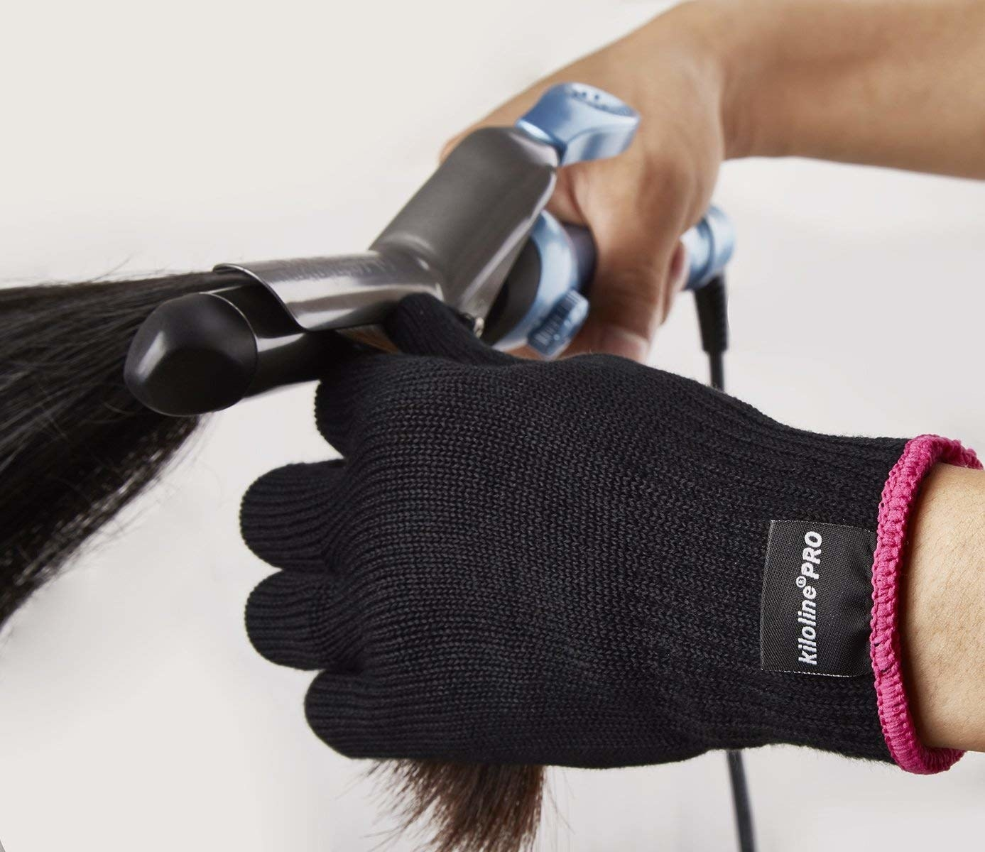 hands wearing the protective gloves holding a strand of hair being curled with a curling iron