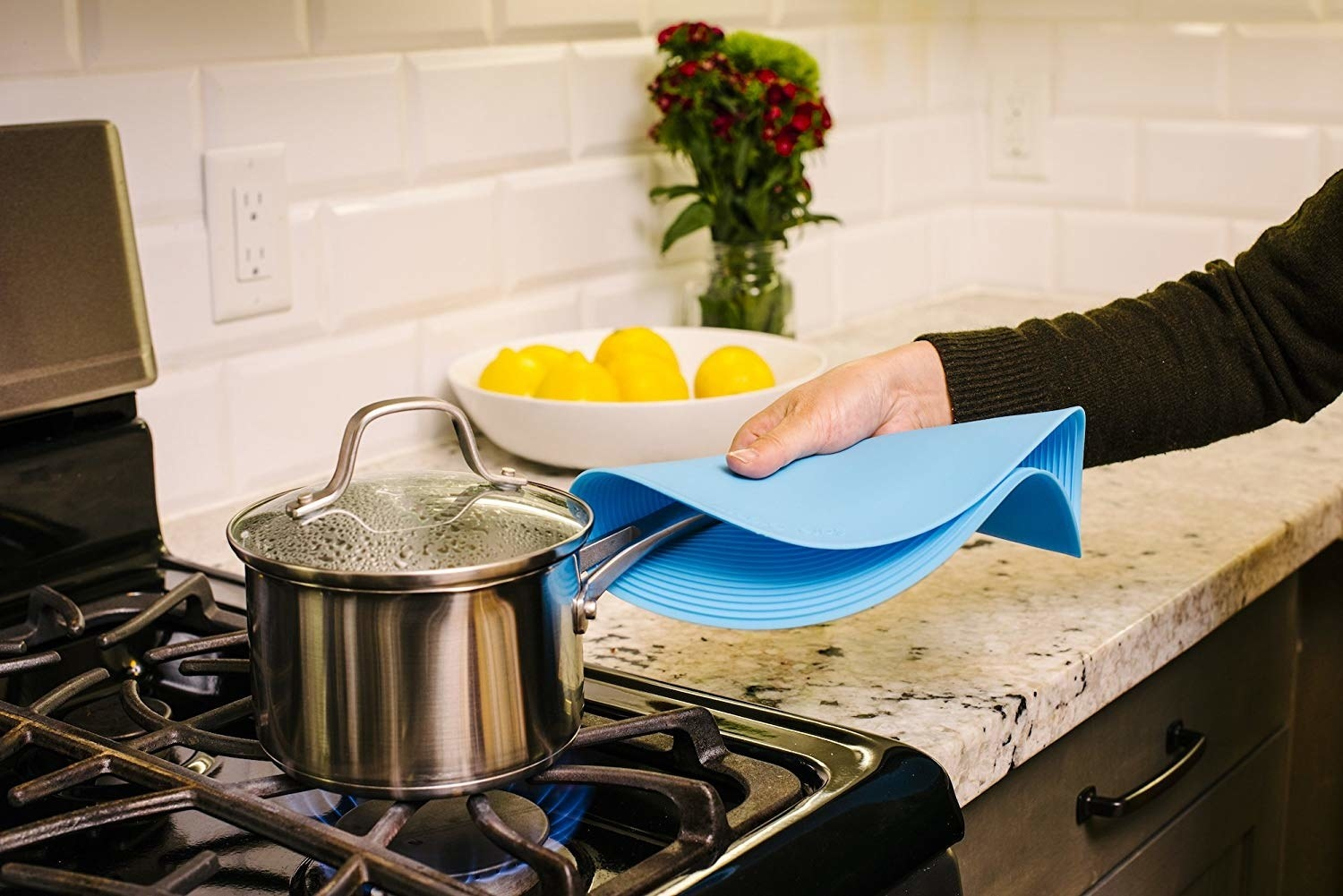 handing using large circular silicone grabber to grab a cooking pot's handle