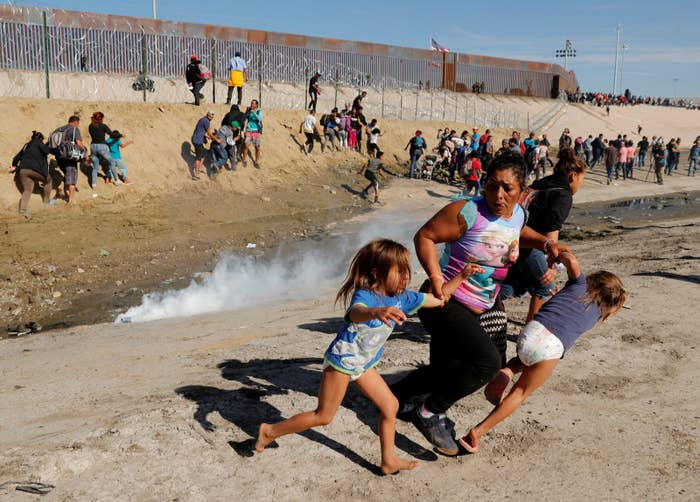 Maria Lila Meza Castro of Honduras runs away from tear gas with her 5-year-old twin daughters.