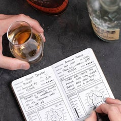 person writing in. whiskey note book