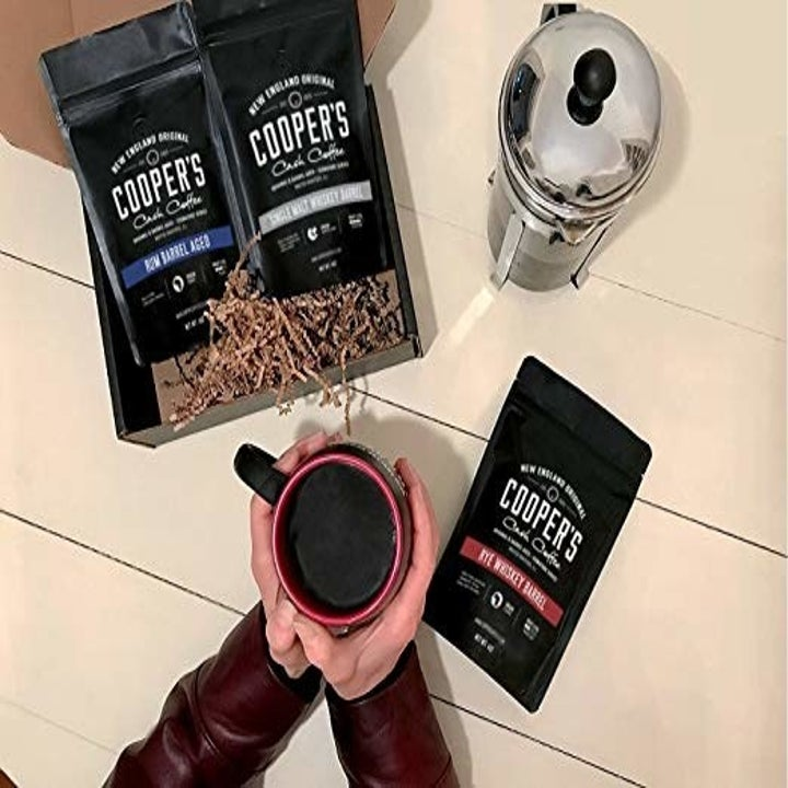 person holding a cup of coffee and the different bags spread out