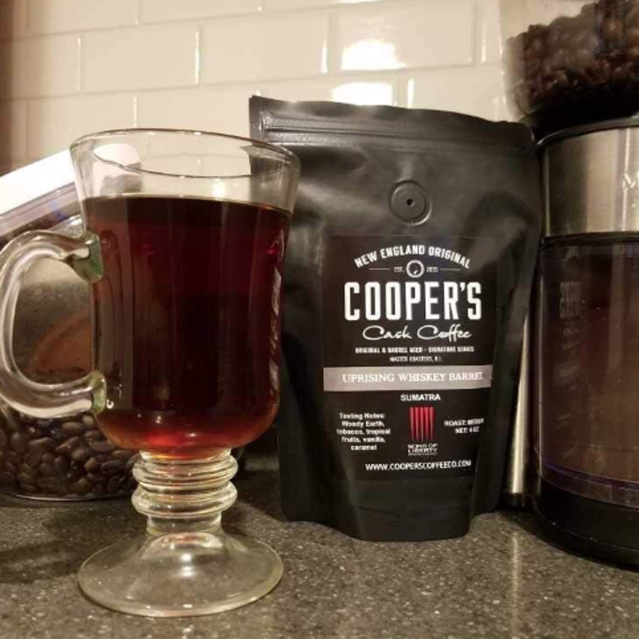 the Cooper's Cask coffee bag next to a cup of coffee