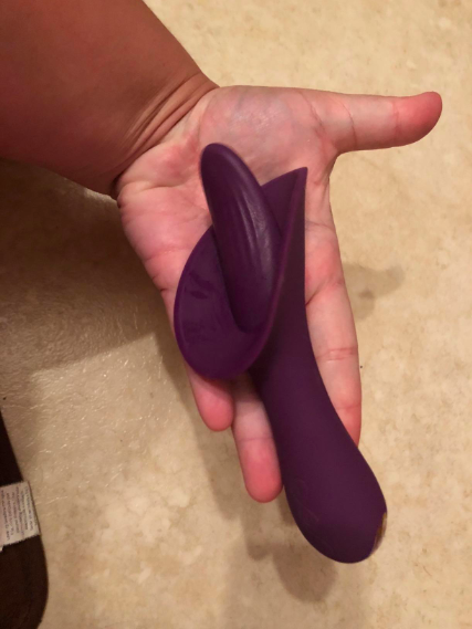 a reviewer holding the tongue-shaped vibe