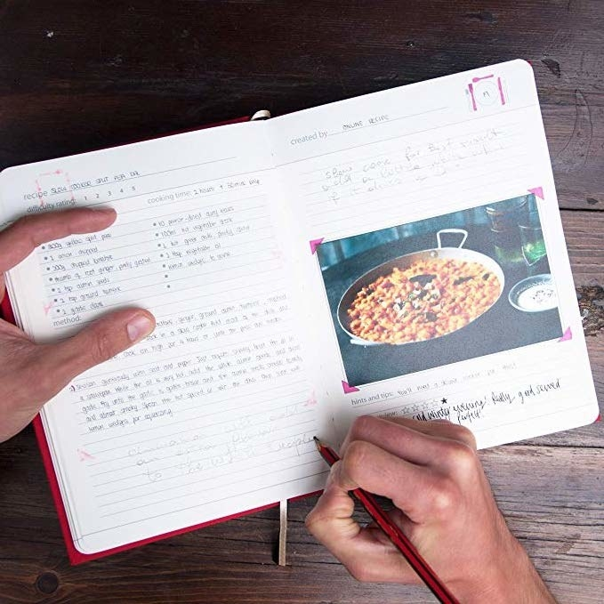 person writing in their cookbook
