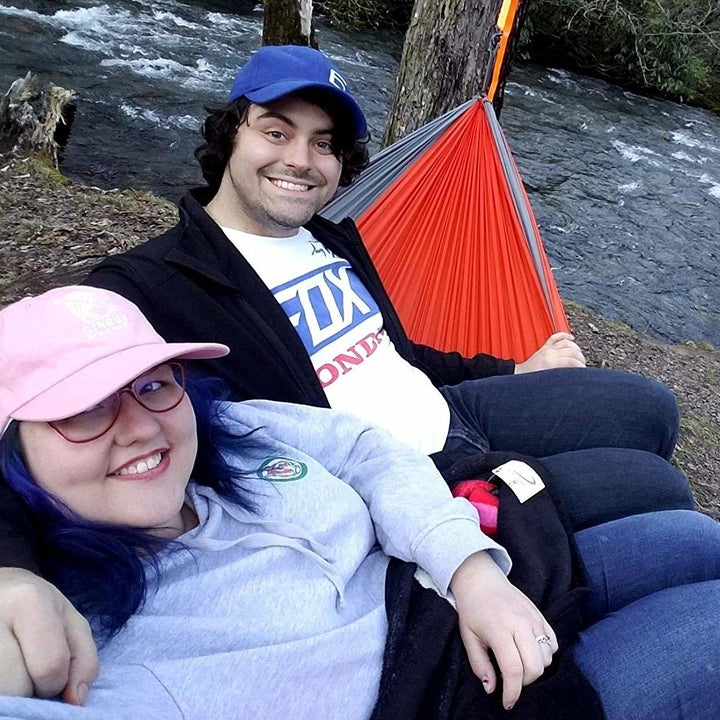 Couple sitting in hammock by river