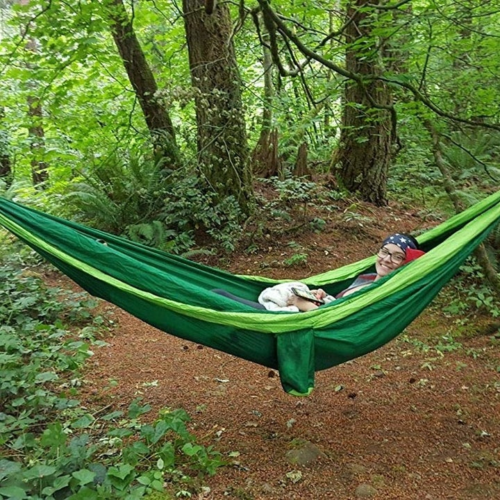 Person laying inside hammock hung between two trees