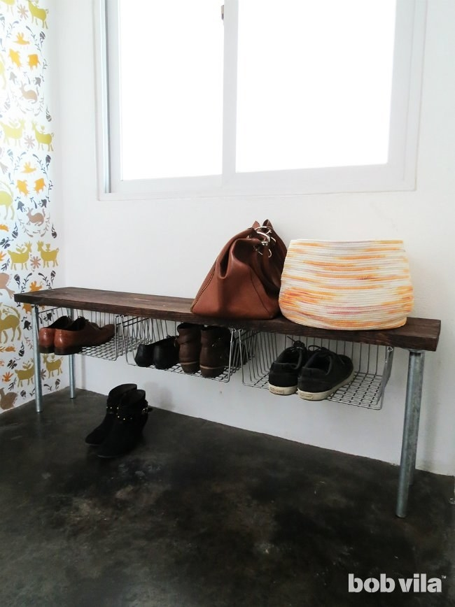 If you want to DIY the whole bench, the project is pretty simple. Just glue two boards together and use trigger clamps to reinforce the bond. Once the glue is dry, install the pipes and hang small c-hooks on the underside of the bench for the baskets. Learn more here.