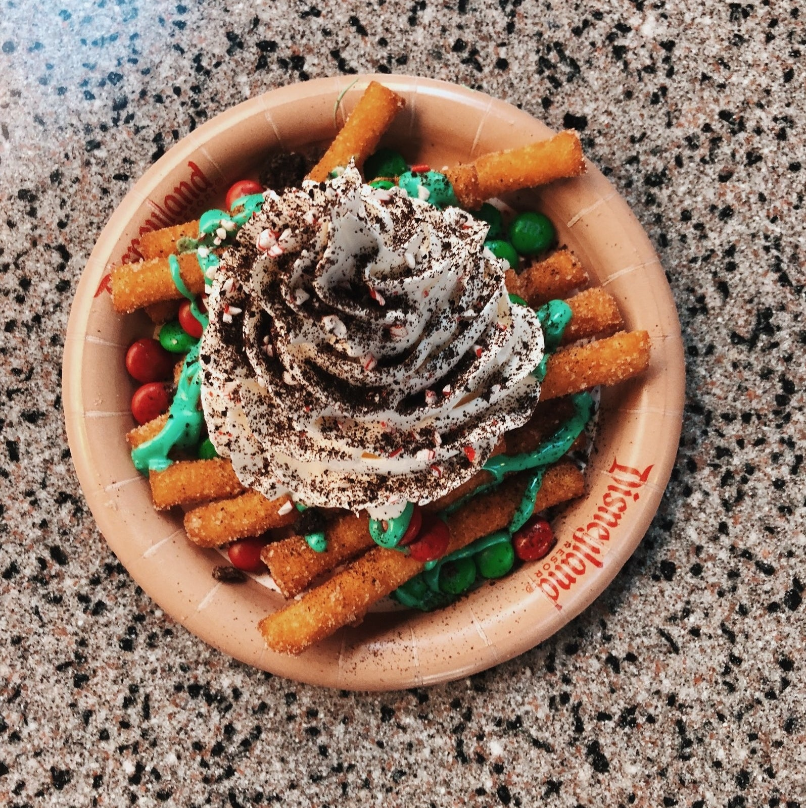 Where you can get it: Award Wieners in Hollywood Land.Why it's so good: So this is similar to the Cookies & Cream Funnel Cake Fries offered during Halloween time, it's funnel cake with topped with crushed cookies, peppermint icing, M&M type chocolates, crushed candy cane, and whipped cream. It is INDULGENT, to say the least. But this it is super delicious!  Get it if: You want to treat yourself to something super decadent.