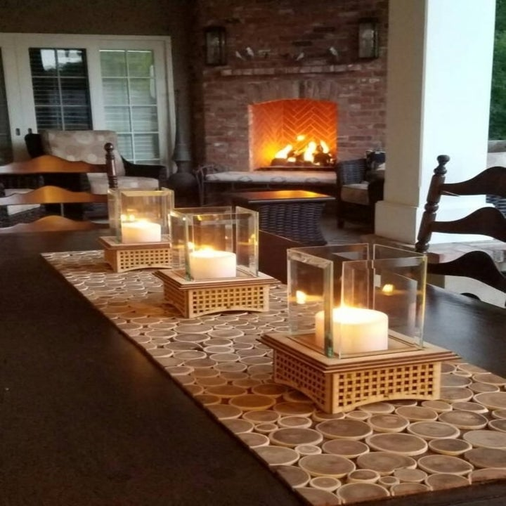 the wooden tabletop fireplace being used as a candle holder