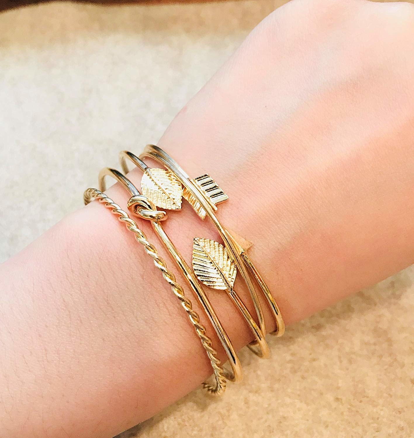A wrist with four bracelets: a twisted one, a knotted bangle, an open bangle with leaves on the ends, and an arrow-shape one