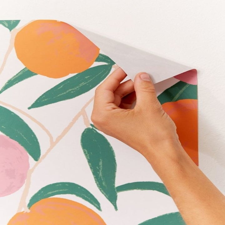 a hand peeling back the removable wallpaper
