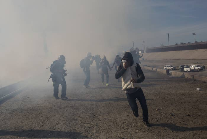 Migrants run from tear gas launched by US agents on Nov. 25.