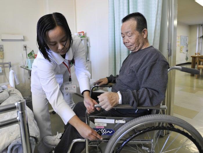 (写真:病院で働くフィリピン人の看護師助手)入管法改正案によると、新たに二つの在留資格が作られる。まず、一定の知識や日本語力で働ける「特定技能1号」と、さらに深い知識や技能を求める「特定技能2号」の2種類だ。来年度から運用が始まる予定なのは、特定技能1号だ。政府は、この資格で入国した外国人が、以下の14業種で働くことを想定している。各省庁が、担当する業界から要望を受けて選定したという。* 介護* ビルクリーニング業* 農業* 漁業* 飲食料品製造業* 外食業* 素形材産業* 産業機械製造業* 電子・電気機器関連産業* 建設業* 造船・舶用工業* 自動車整備業* 航空業* 宿泊業政府は11月14日の衆院法務委員会理事懇談会で、初年度に最大4万7550人、5年間で最大34万5150人を受け入れるとの試算を提示した。初年度の最大受け入れ人数が最も多いのは農業の7300人。次いでビルクリーニング業の7000人。介護業と外食業は5000人だった。初年度から5年目までの累計で介護業が6万人、外食業が5万3000人、建設業が4万人を受け入れる。なお政府の試算では、これら14業種では現時点で58万6400人の人手が不足しており、5年後には145万5000人が不足する見通しだという。「特定2号」は先送り一方、「特定技能2号」の運用開始は、数年後に先送りされる見通しだ。それぞれの産業で、何をもって「熟練した技能」とするかの定義も、それを図る試験の内容も、まだ詰まっていない状況だからだ。菅義偉官房長官はまた、11月14日の記者会見で、「特定技能2号」は「建設業」と「造船・船用工業」の2業種に絞る考えを示した。