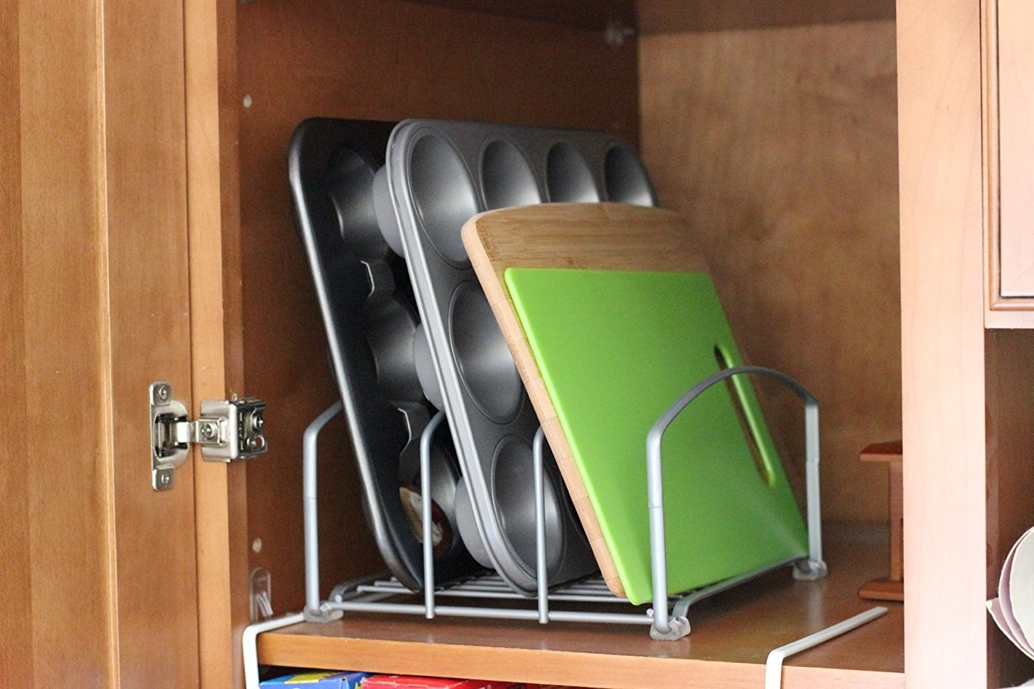 organizer that holds cutting boards and baking pans vertically in cabinet