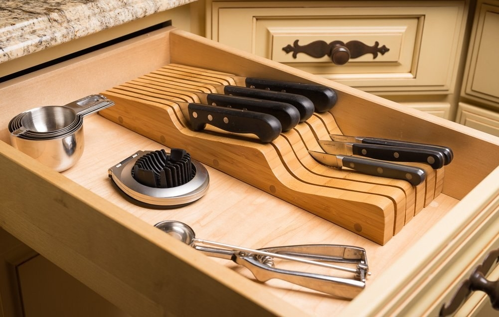 open drawer with wood knife organizer inside to protect each blade