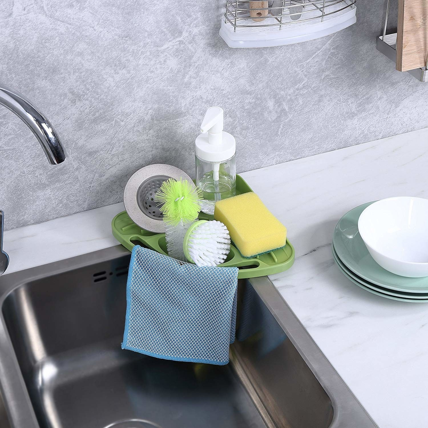 kitchen sink with a corner caddy with a dishcloth hanging from it and dish brushes, a sponge, and hand soap contained on it
