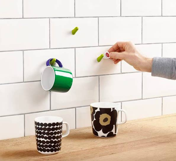 person putting a hook with the moldable glue on a subway tile wall to hang up coffee mugs