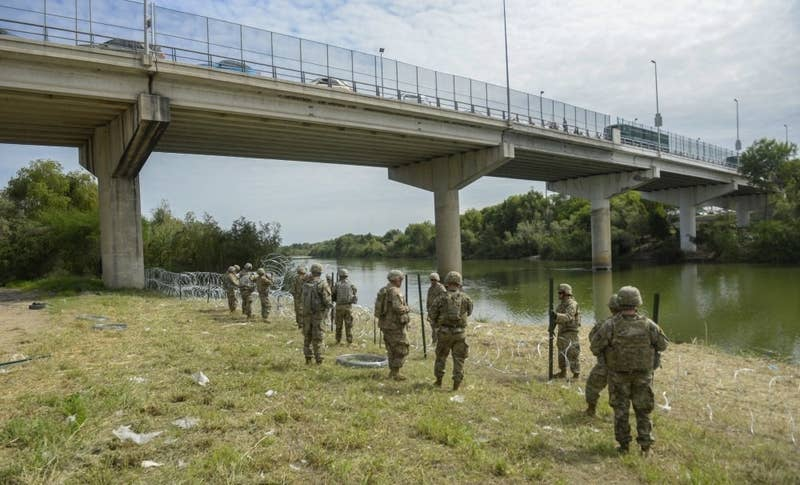 Soldiers from the 97th Military Police Battalion and the 41st Engineer Company from Fort Riley, Kansas, string concertina wire near the Mexican border.