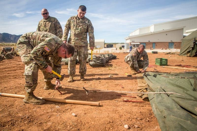 A soldier from the 309th Military Intelligence Battalion hammers a stake into the ground at Fort Huachuca, Arizona.