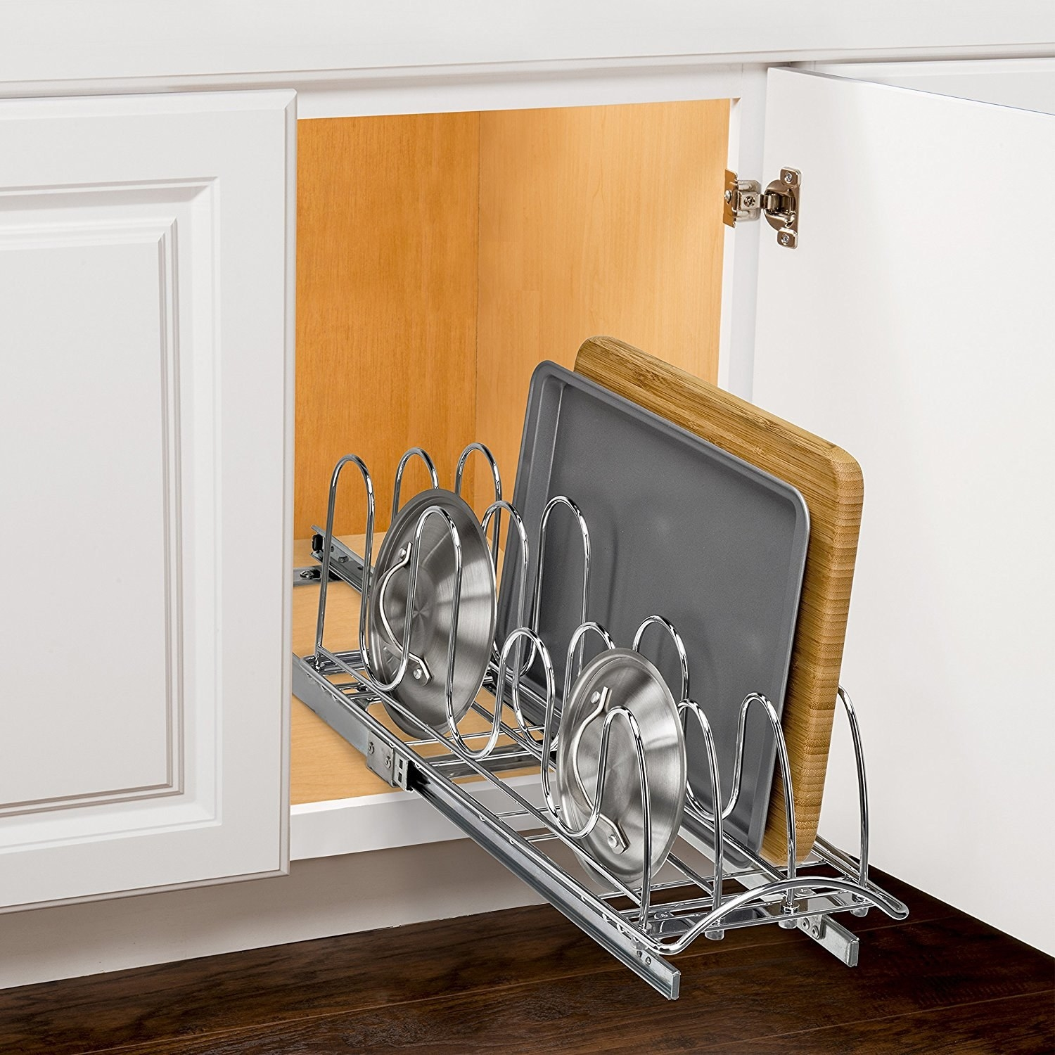 open kitchen cabinet with rollout rack for holding pot lids and baking sheets
