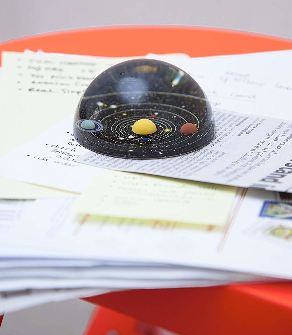 solar system dome shape paperweight on stack of papers
