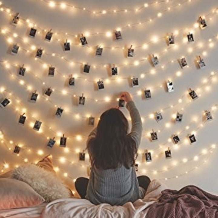 person putting photos onto clips on the string lights on a wall