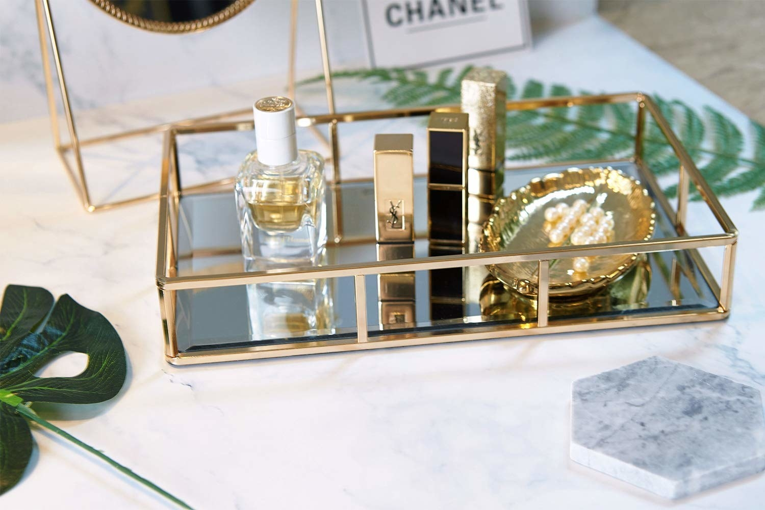 the gold tray with a mirror bottom filled with makeup, nail polish, and jewelry