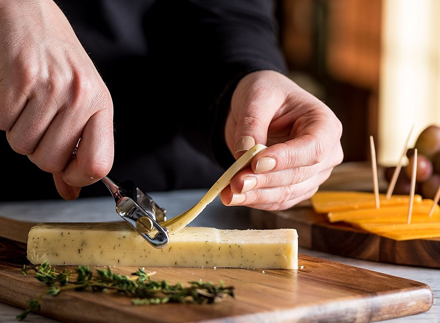 A model slicing cheese from a block with the stainless steel slicer