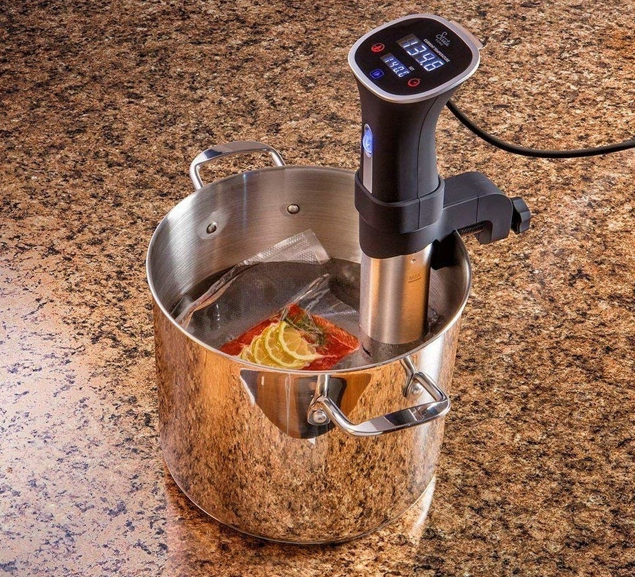 "Sous vide, which means ""under vacuum"" in French, refers to the process of vacuum-sealing food in a bag, then cooking it to a very precise temperature in a water bath. This method ensures maximum tenderness and moisture retention — without worry of overcooking.Promising review: ""I like the simplicity of this thing. It doesn't connect to a phone, and it only has half degree adjustments. Do you need those things though? It does take a bit longer to reach the desired temperature, particularly anything over 165°F, but it holds the temp once it gets there. I've cooked corned beef for 42 hours, flatiron steak for 24 hours, strips for two hours without a hiccup. Individual cheesecakes, Starbucks egg-bite knockoffs, sealing mason jars, the best asparagus you've ever had. Everything I've thrown at this thing has impressed me so far."" —Mike R.Get it from Amazon for $69.99."