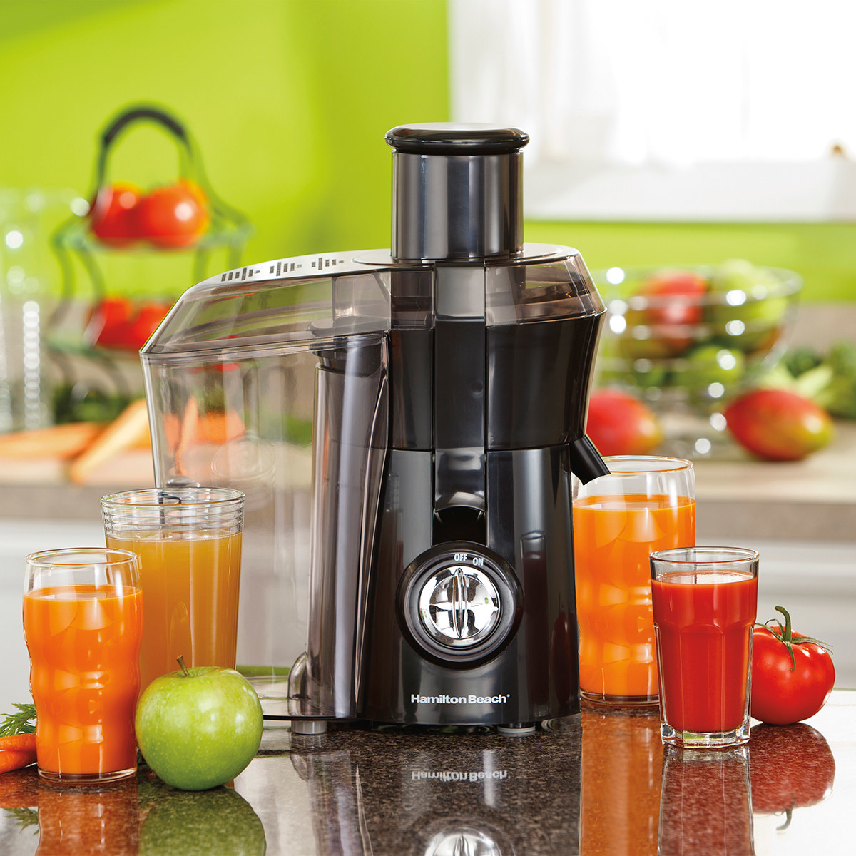 The juice extractor on a counter surrounded by cups of different juice as well as apples and tomatoes