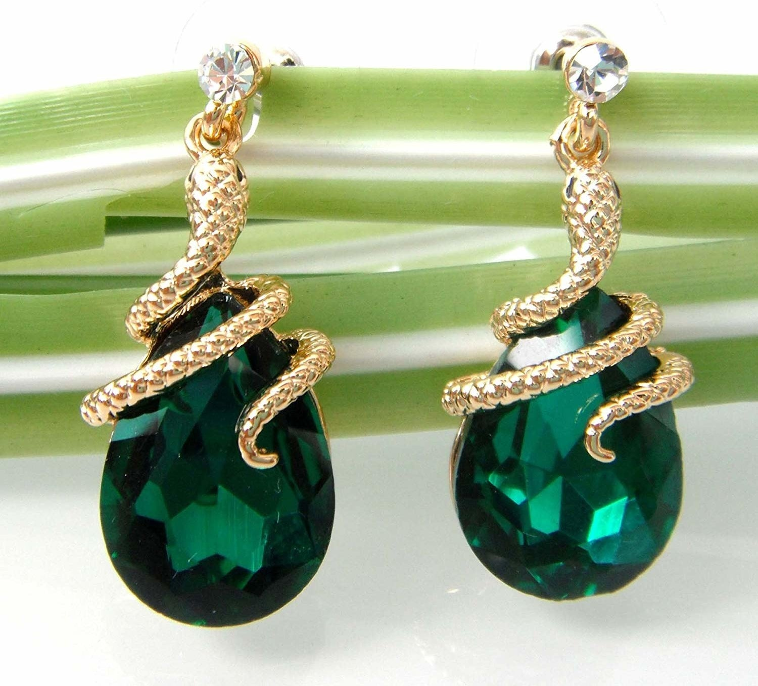 The dangle earrings with teardrop green stones and snakes wrapped around the top